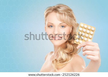 people, beauty, healthcare and medicine concept - happy young woman holding package of pills over blue background - stock photo