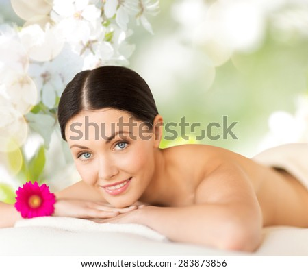 people, beauty, spa and body care concept - happy beautiful woman lying on massage desk over green natural cherry blossom background - stock photo