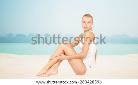 people, beauty, spa and resort concept - beautiful woman in cotton underwear over infinity edge pool background - stock photo