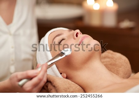 people, beauty, spa, cosmetology and skincare concept - close up of beautiful young woman lying with closed eyes and cosmetologist applying facial mask by brush in spa - stock photo