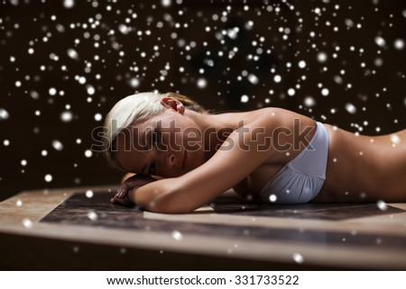people, beauty, spa, healthy lifestyle and relaxation concept - beautiful young woman lying on hammam table in turkish bath with snow effect - stock photo