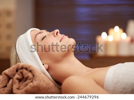 people, beauty, spa, healthy lifestyle and relaxation concept - close up of beautiful young woman lying with closed eyes in spa - stock photo