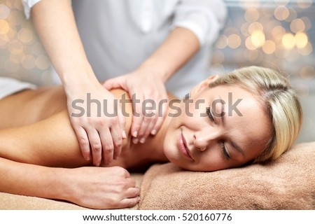 people, beauty, spa, healthy lifestyle and relaxation concept - close up of beautiful young woman lying with closed eyes and having hand massage in spa
