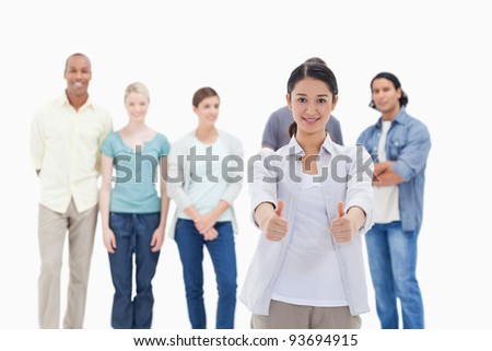 People behind a woman smiling with her the thumbs-up against white background - stock photo