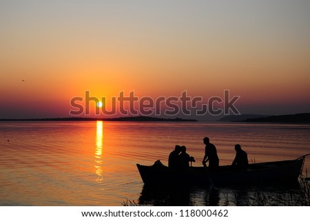 people boat on lake during sunset  - stock photo
