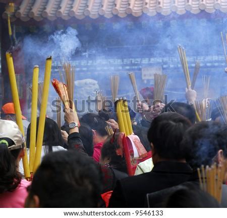 People burning incense at Wong Tai Sin temple in Hong Kong at Chinese New Year - stock photo