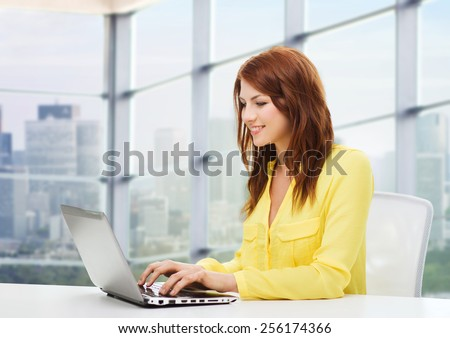 people, business and technology concept - smiling young woman with laptop computer sitting at table over office window background - stock photo