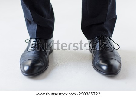 people, business, fashion and footwear concept - close up of man legs in elegant shoes with laces or lace boots - stock photo