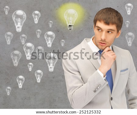 people, business, idea and doubts concept - young businessman thinking over gray background and light bulbs - stock photo