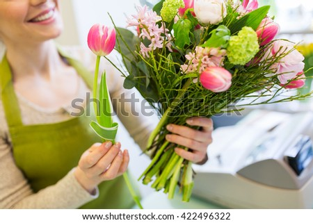 people, business, sale and floristry concept - close up of happy florist woman making bunch at flower shop - stock photo