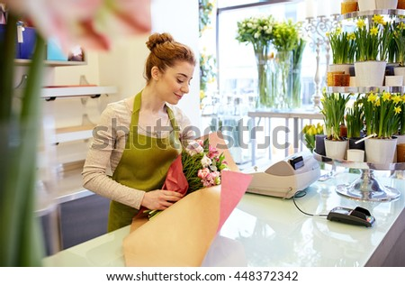people, business, sale and floristry concept - happy smiling florist woman wrapping bunch into paper at flower shop - stock photo