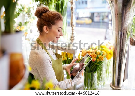 people, business, technology, sale and floristry and concept - happy smiling florist woman with tablet pc computer at flower shop - stock photo