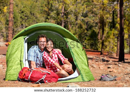 People camping in tent - happy backpacking couple in forest. Campers smiling happy outdoors in forest. Happy multiracial couple having fun relaxing in outdoor activity. Asian woman, Caucasian man - stock photo