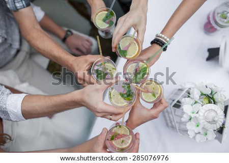 people celebrate. Clink glasses with the drink - stock photo