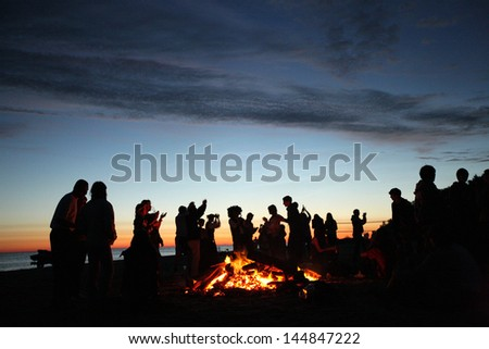 People celebrating in evening at the beach next to fire - stock photo