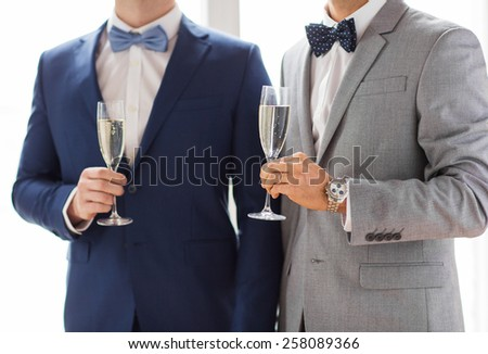 people, celebration, homosexuality, same-sex marriage and love concept - close up of happy married male gay couple in suits and bow-ties drinking sparkling wine from glasses on wedding - stock photo