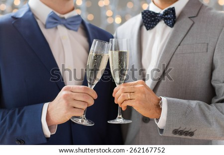 people, celebration, homosexuality, same-sex marriage and love concept - close up of happy married male gay couple drinking sparkling wine on wedding over holidays lights background - stock photo