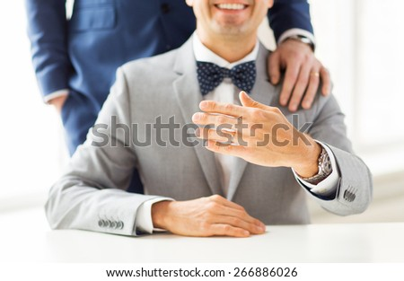 people, celebration, homosexuality, same-sex marriage and love concept - close up of male gay couple with wedding rings on putting hand on shoulder - stock photo