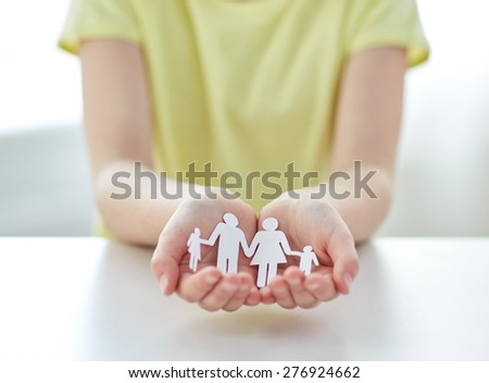 people, charity and care concept - close up of happy girl hands holding paper family cutout at home - stock photo