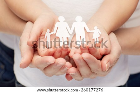 people, charity, family and care concept - close up of woman and girl hands holding paper family cutout