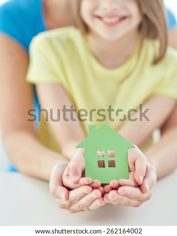 people, charity, family and home concept - close up of woman and girl holding green paper house cutout in cupped hands