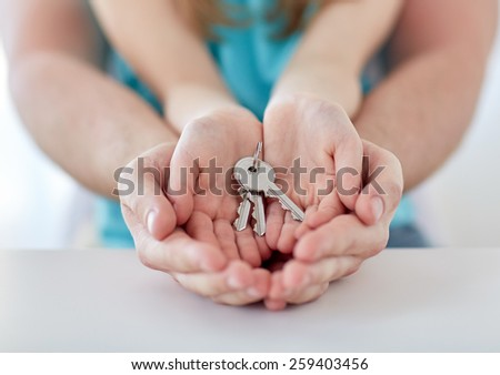 people, charity, family, real estate and home concept - close up of man and girl holding house keys in cupped hands - stock photo