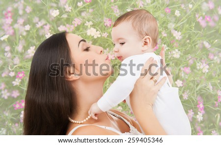 people, childhood, royalty and happiness concept - happy mother kissing and holding baby over floral background - stock photo