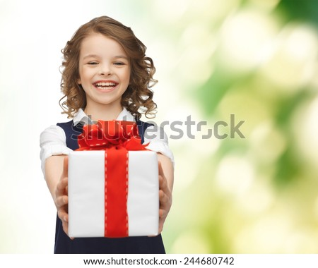 people, childhood, summer and holidays concept - happy smiling girl with gift box over green background - stock photo
