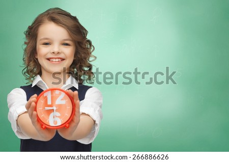 people, childhood, time and punctuality concept - happy girl with alarm clock over green chalk board background - stock photo