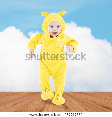 people, children, achievement and happiness concept - happy baby in yellow suit making first steps over wooden floor and blue sky background - stock photo