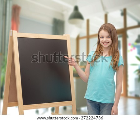 people, children, advertisement and education concept - happy little girl with blackboard and chalk over school class room background - stock photo