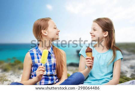 people, children, friends and friendship concept - happy little girls eating ice-cream over summer beach background - stock photo