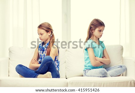 people, children, friends and friendship concept - quarreled angry little girls sitting on sofa back to back at home - stock photo