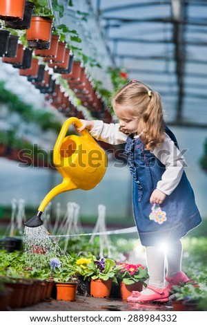 people - children, gardening and profession concept - happy children  taking care of flowers in greenhouse - stock photo