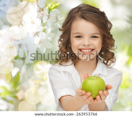 people, children, healthy eating, ecology and food concept- happy girl holding green apple over summer or spring garden background - stock photo