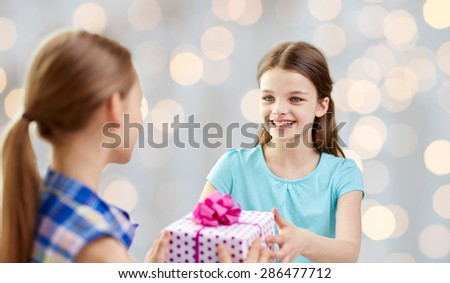 people, children, holidays, friends and friendship concept - happy little girls with birthday present over lights background - stock photo