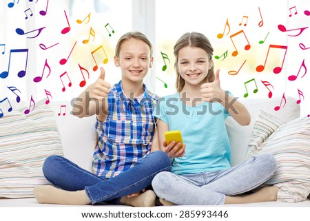 people, children, technology, friends and friendship concept - happy little girls with smartphone and earphones listening to music and showing thumbs up at home over colorful musical notes background - stock photo