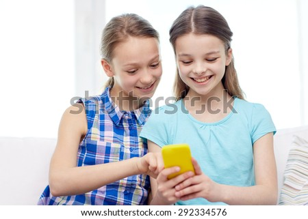 people, children, technology, friends and friendship concept - happy little girls with smartphone sitting on sofa at home - stock photo