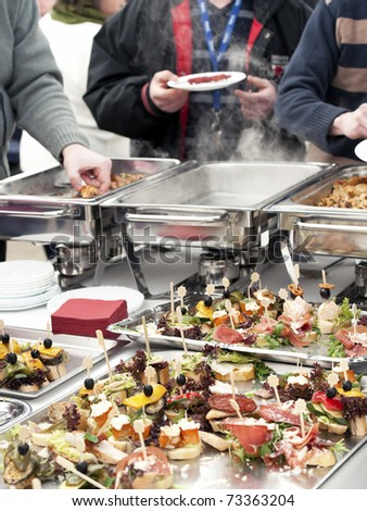 People choosing food from buffet on a business event - stock photo