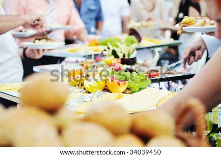 people choosing food from table on catering and buffet party on business seminar conference or wedding - stock photo