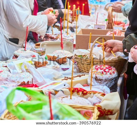 People come to church consecrate Easter cakes and eggs, lit church candles, inserted into the cakes - stock photo