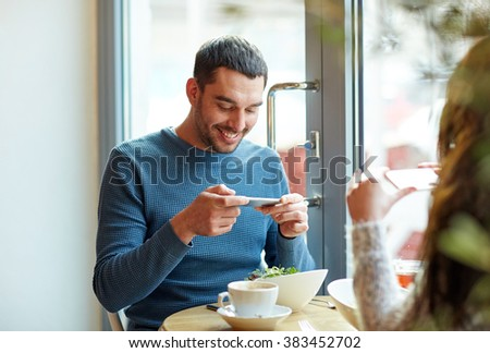 people, communication and dating concept - happy couple with smartphones picturing food at cafe or restaurant - stock photo
