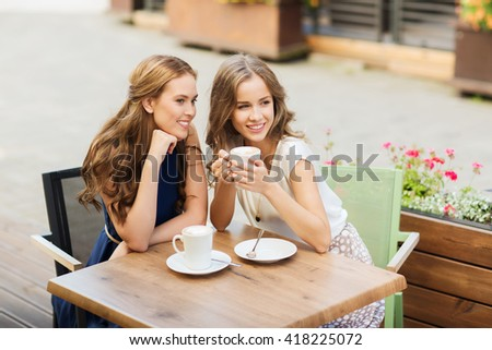 people, communication and friendship concept - smiling young women drinking coffee and talking at outdoor cafe - stock photo