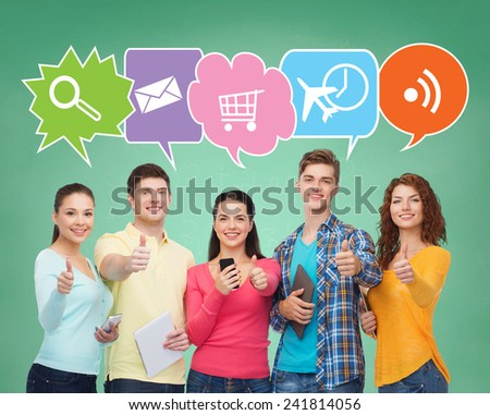 people, communication, school, gesture and technology concept - smiling friends with smartphones and tablet pc computers showing thumbs up over green board background with doodles - stock photo