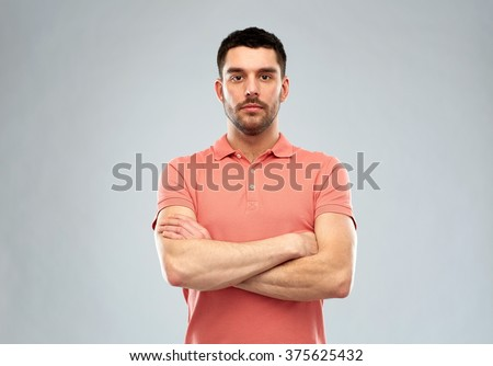 people concept - serious young man in polo t-shirt with crossed arms over gray background - stock photo