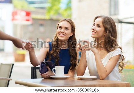 people, consumerism, lifestyle and friendship concept - smiling young women giving credit card to waiter hand and paying for coffee at outdoor cafe - stock photo