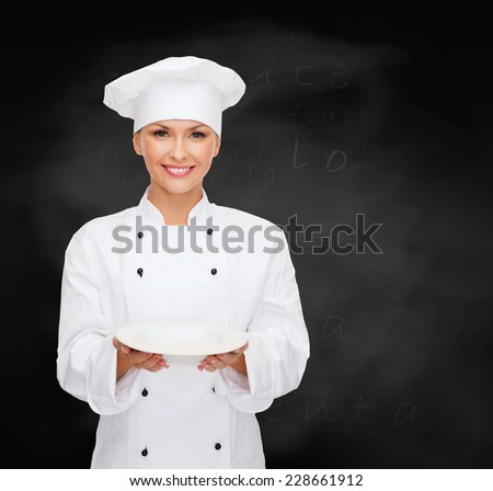 people, cooking and food concept - smiling female chef, cook or baker with empty plate over blackboard background - stock photo