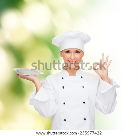 people, cooking and food concept - smiling female chef, cook or baker with plate showing ok sign over green background - stock photo