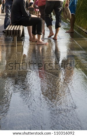 People cooling their feet on a pavement with running water. - stock photo