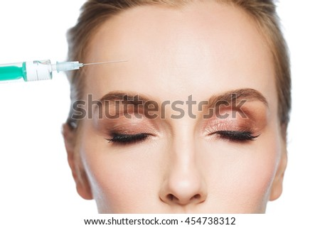 people, cosmetology, plastic surgery, anti-aging and beauty concept - beautiful young woman face and syringe making lifting injection to forehead over white background - stock photo